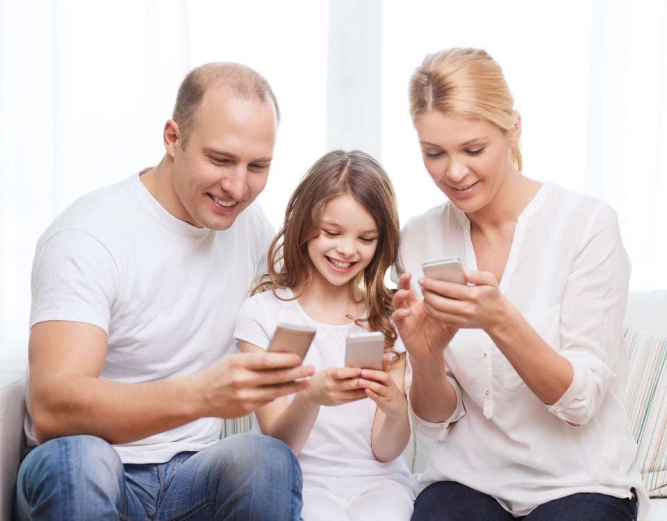 27109263 - family, child, technology and home concept - smiling parents and little girl with smartphones at home